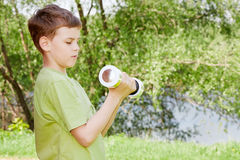 Boy does exercises with dumbbell outdoors Royalty Free Stock Photos