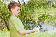 Boy does exercises with dumbbell in park Royalty Free Stock Photo