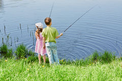 Boy and his sister fish in pond Stock Photo