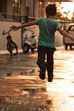 Boy in Green T Shirt Running on Wet Road during Daytime Royalty Free Stock Photo