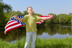 Boy stands on bank of pond with eyes closed. Boy in green t-shirt stands on bank of pond with eyes closed against the sun and holds unfolded flag behind his back Stock Images