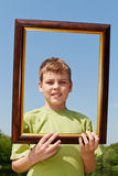 Boy stands outdoors, holding picture frame Stock Images