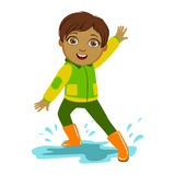 Boy In Green And Yellow Jacket, Kid In Autumn Clothes In Fall Season Enjoyingn Rain And Rainy Weather, Splashes And Stock Image