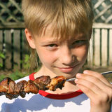Boy with grilled meat Stock Image