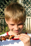 Boy with grilled meat Royalty Free Stock Photo