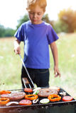 Boy grilling vegetable. Royalty Free Stock Photography
