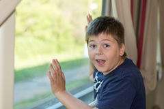 Boy grimaces standing at train window Royalty Free Stock Image