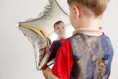 Boy grimacing and playing the ape with star-shaped balloons in s. Tudio. Kid looks and rejoices at his reflection in foil balloon. Child laughing looking at the Stock Photography