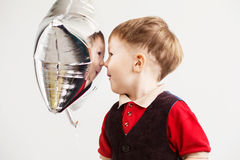 Boy grimacing and playing the ape with star-shaped balloons. In studio. Kid looks and rejoices at his reflection in foil balloon. Child laughing looking at the Royalty Free Stock Photos