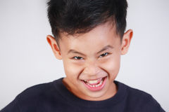 Boy with Grin Face. Portrait of young Asian boy with naughty evil grin smile Stock Image