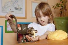 Boy Grinding Dough Stock Photography