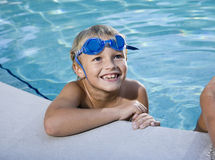 Boy grinning, hanging on to side of swimming pool Royalty Free Stock Images