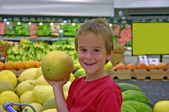 Boy in Grocery Store. Boy holding a melon in produce department Royalty Free Stock Image