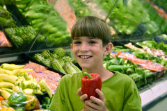Boy in Grocery Store. Boy holding a pepper in produce department Stock Photo