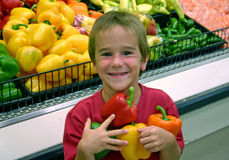 Boy in Grocery Store. Boy holding a pepper in produce department Royalty Free Stock Photo
