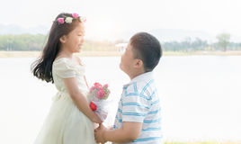 Boy groom handed a bouquet of roses to the little girl bride Stock Image