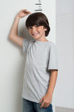 Boy growing tall and measuring himself. Closeup of little boy measuring height himself against white wall. Boy growing tall. Smiling cute boy measures his height Royalty Free Stock Images