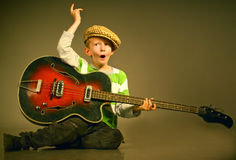 The boy with a guitar. The young boy emotionally plays on a guitar Royalty Free Stock Photo