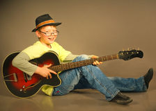 The boy with a guitar. The young boy emotionally plays on a guitar Stock Photos