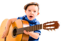 Boy and guitar. Child, 5 years old, plays guitar with emotion, white background Royalty Free Stock Image