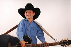 Boy with guitar and cowboy hat Royalty Free Stock Photography