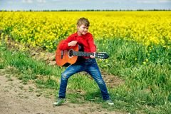 Boy with acoustic guitar outdoors. A boy with a guitar on the nature of the concept of children`s music education stock photos
