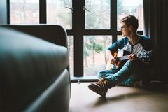 Boy with guitar sits on the floor at cozy home, moody day light royalty free stock photography