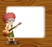A boy with a guitar standing in front of the empty template Royalty Free Stock Photography
