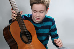Boy with guitar. Boy tries to play guitar Stock Image