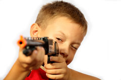 Boy and a gun. The boy looks in a gun sight, he wishes to hit the mark Stock Image