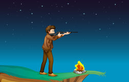 A boy with a gun at the cliff with a campfire Royalty Free Stock Photo