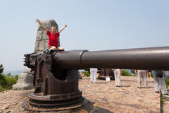 Boy on a gun in the old Russian fort Stock Photo