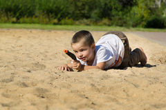 Boy with a gun on playground. A little boy in a t-shirt with a gun in the sand on the playground Royalty Free Stock Image