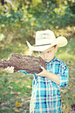 Boy with Gun. A young boy with a cowboy hat, blue plaid shirt, holding a pretend gun made out of tree bark that he found in the forest Royalty Free Stock Photo