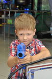 Boy with guns in the hall game machines Royalty Free Stock Images