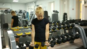 Boy in the gym with dumbbells.  stock footage
