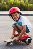 Boy with a gyro scooter and skateboard, outdoors Royalty Free Stock Images