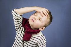 The boy had a headache. On a blue background Royalty Free Stock Photos