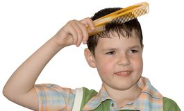 The boy hair combs (hygiene). On a white background-old boy with a hairbrush Stock Images