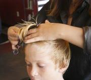 Boy Haircut. Boy getting his hair cut at a popular salon and barbershop Royalty Free Stock Photography