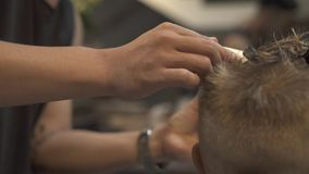 Boy hairstyle concept. Childen hairdresser cutting hair to little boy with electrical shaver in barber salon. Boy. Haircut with hair machine close up. Barber stock video footage