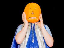 Boy in Halloween costume with a mask from a pumpkin Stock Images