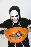 Boy In Halloween Outfit Holding Bowl Of Candies Stock Photography