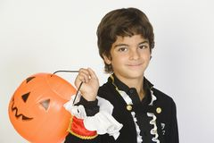 Boy In Halloween Outfit Holding Jack-O-Lantern Stock Photo