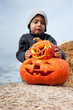 Boy and halloween pumpkins Stock Photos