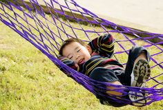 Boy in hammock. A picture of a little chinese boy laughing and having great fun in hammock Stock Images