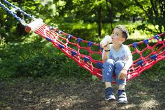 Boy in a hammock with a paper Cup of drink stock image