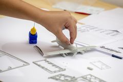 Boy hand assembling plastic model kit of ww2 aircraft. Plane at home. Hobby and leisure Royalty Free Stock Photo