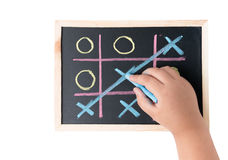 Boy hand drawing a game of tic tac toe on a black chalkboard royalty free stock image