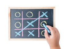 Boy hand drawing a game of tic tac toe on a black chalkboard stock photo